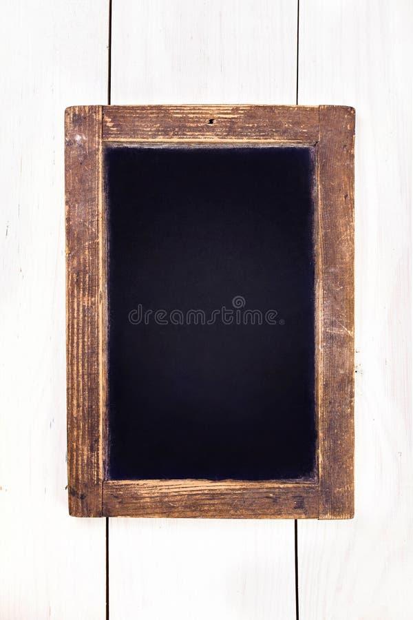 Quadro-negro do vintage que pendura no fundo de madeira. Boa vazia do giz imagem de stock royalty free