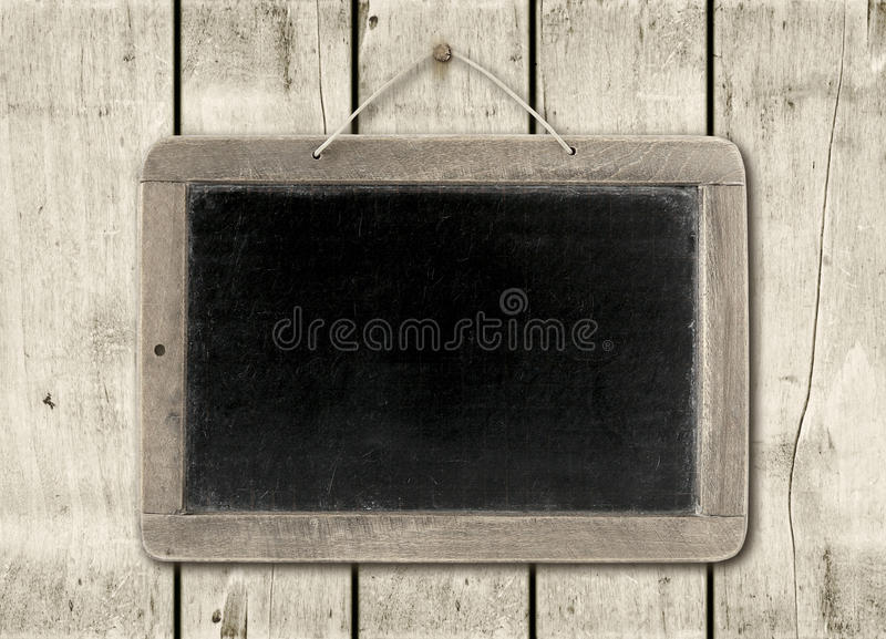 Quadro-negro em um fundo de madeira branco da parede fotografia de stock