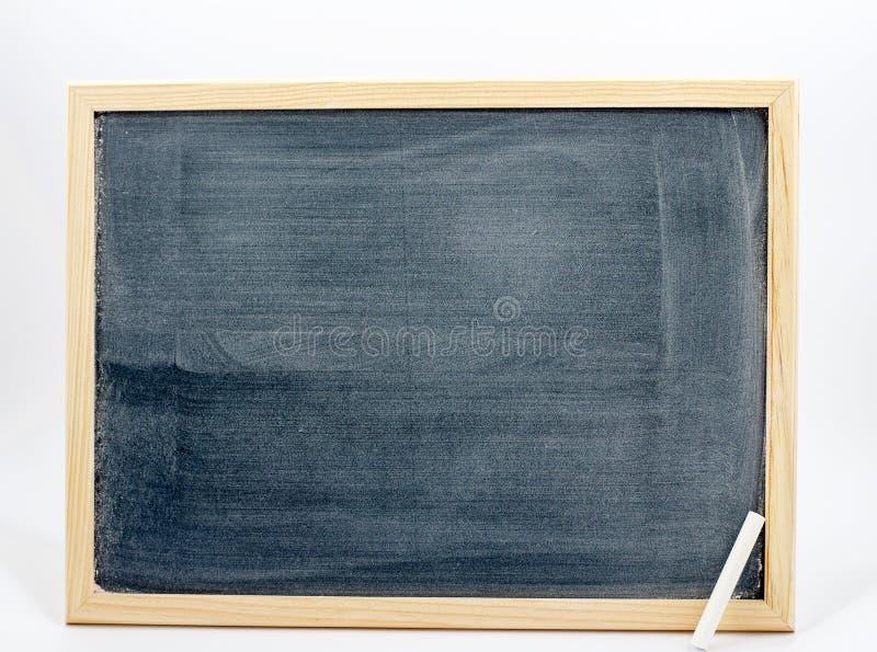 Quadro-negro isolado em um fundo branco com um giz branco no canto foto de stock