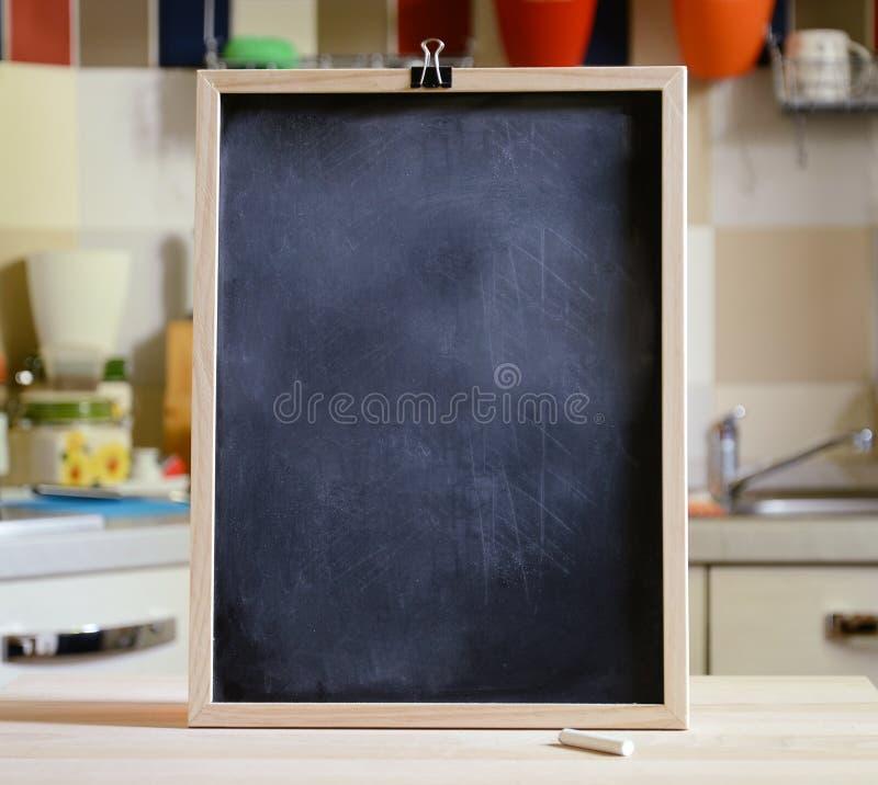 Quadro-negro na tabela de madeira no fundo da cozinha imagens de stock royalty free