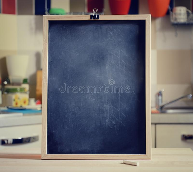 Quadro-negro na tabela de madeira no fundo da cozinha foto de stock