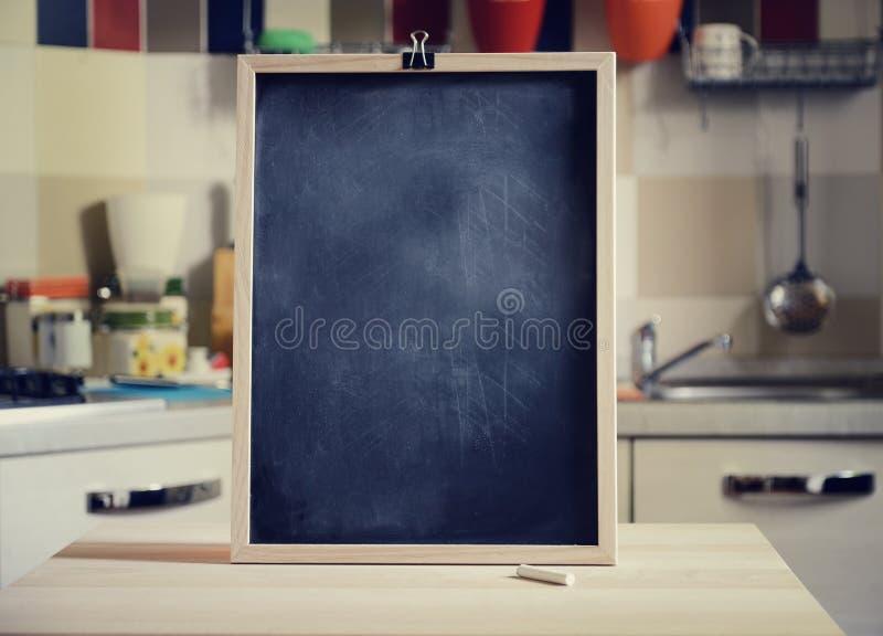 Quadro-negro na tabela de madeira no fundo da cozinha foto de stock royalty free