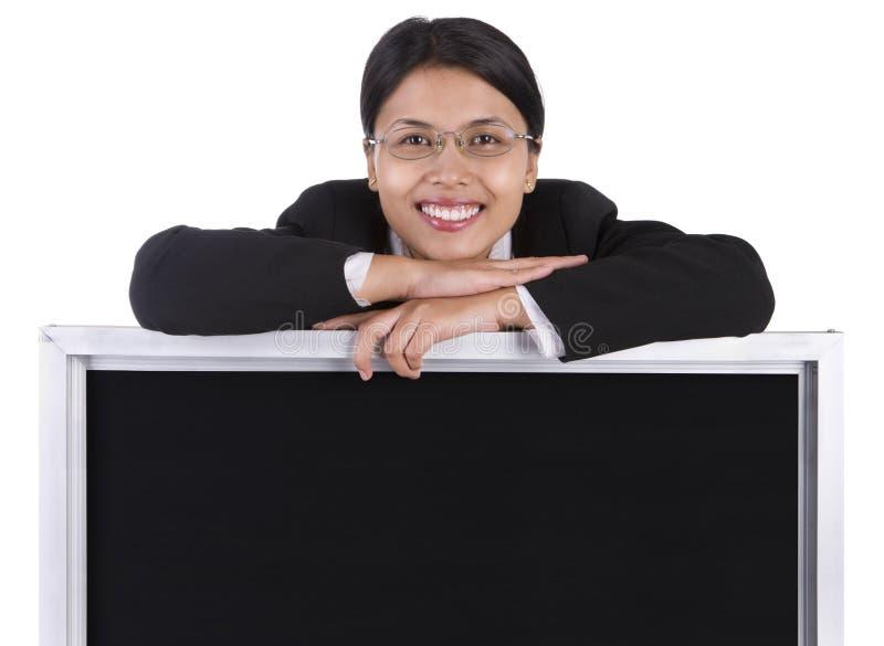 Quadro-negro para afixar a mensagem abaixo da mulher de sorriso fotos de stock royalty free