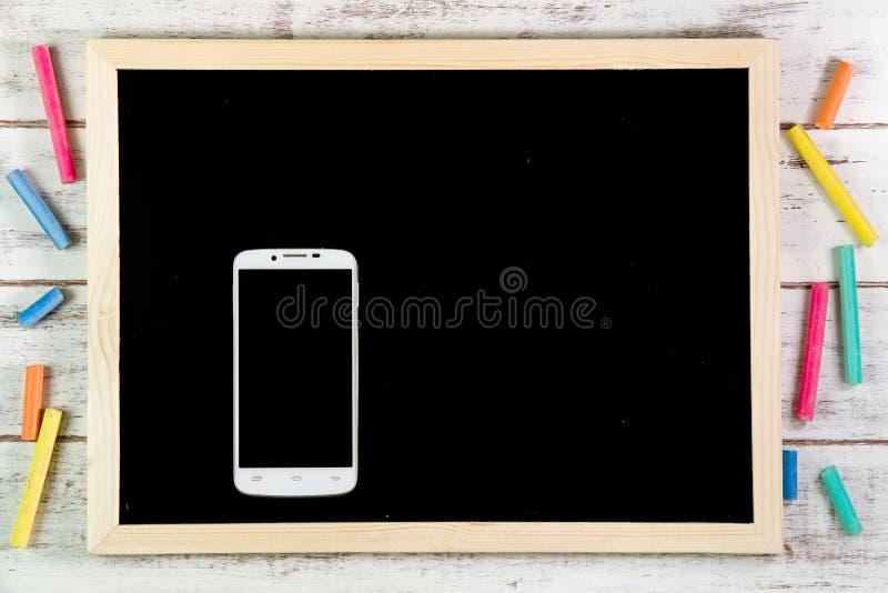 Quadro-negro vazio e telefone esperto na tabela de madeira Molde u trocista fotos de stock