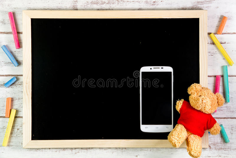 Quadro-negro vazio, Teddy Bear e telefone esperto na tabela de madeira Tem imagens de stock