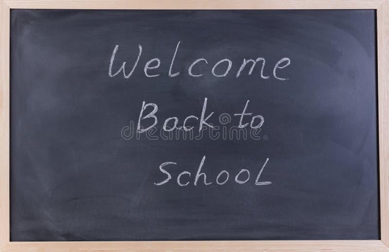 Quadro preto apagado com boa vinda de volta à mensagem da escola para imagem de stock