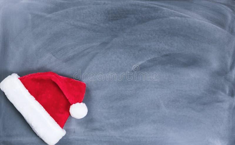 Quadro preto apagado com o tampão de Santa no canto de inferior esquerdo imagem de stock royalty free
