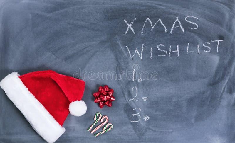 Quadro preto apagado com os bastões do tampão e de doces de Santa mais o texto fotos de stock royalty free