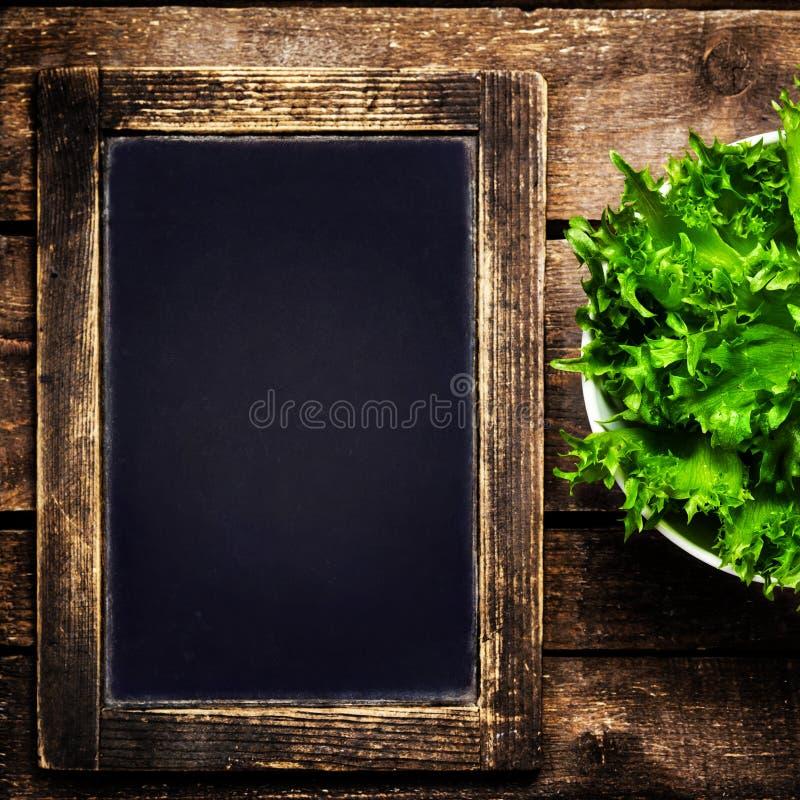 Quadro preto para o menu e salada fresca sobre o fundo de madeira imagens de stock royalty free