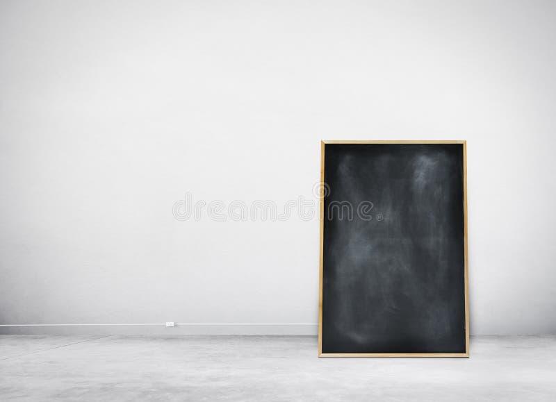 Quadro preto vazio em uma parede branca imagem de stock