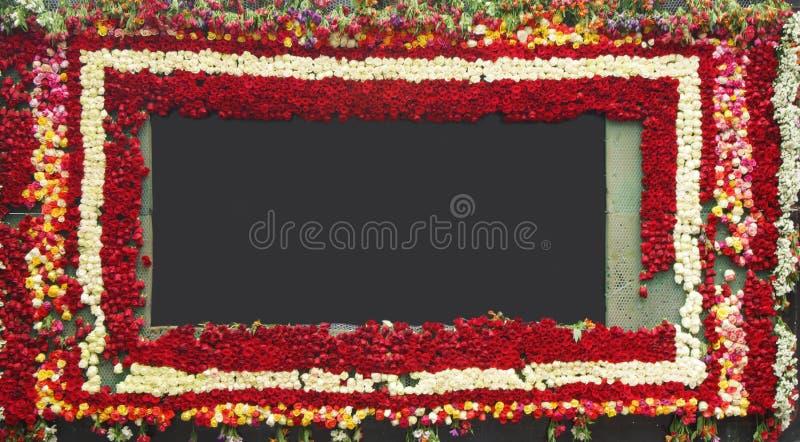 Quadro quadrado grosso decorado com as rosas vermelhas e brancas ao redor em um fundo escuro imagens de stock royalty free