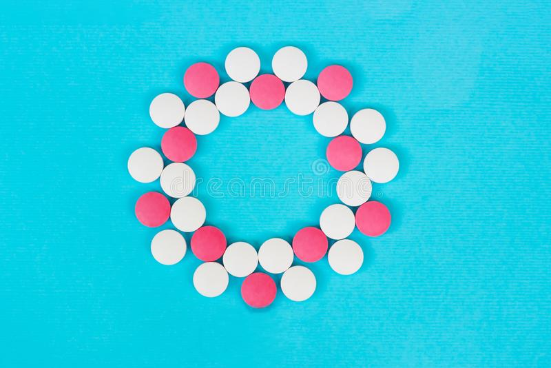 Quadro redondo dos comprimidos brancos e vermelhos em claro - fundo azul imagens de stock
