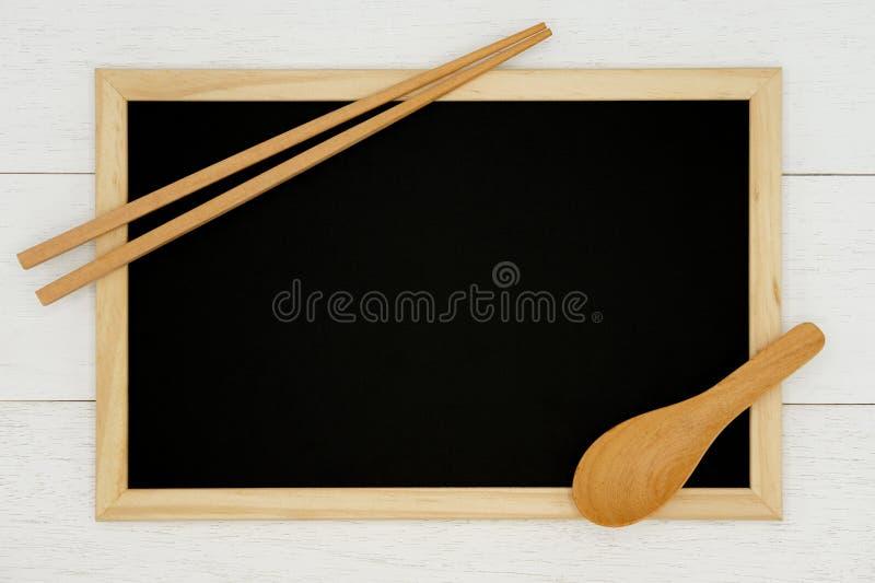 Quadro vazio com colher e o hashi de madeira no fundo de madeira branco da prancha imagem de stock