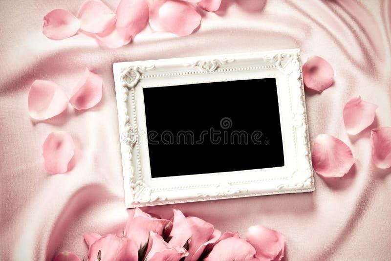 Quadro vazio da foto com uma pétala de rosas cor-de-rosa doce do ramalhete no sof imagem de stock royalty free