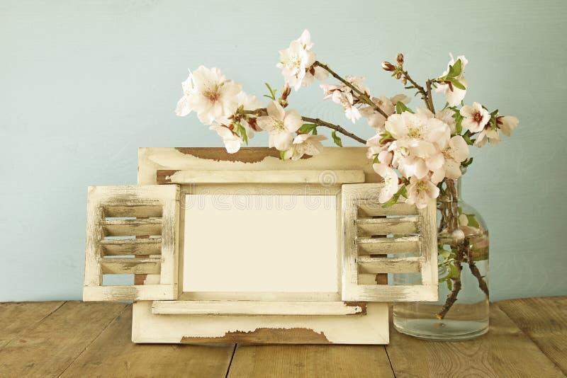 Quadro vazio da foto do vintage ao lado das flores da mola imagem de stock