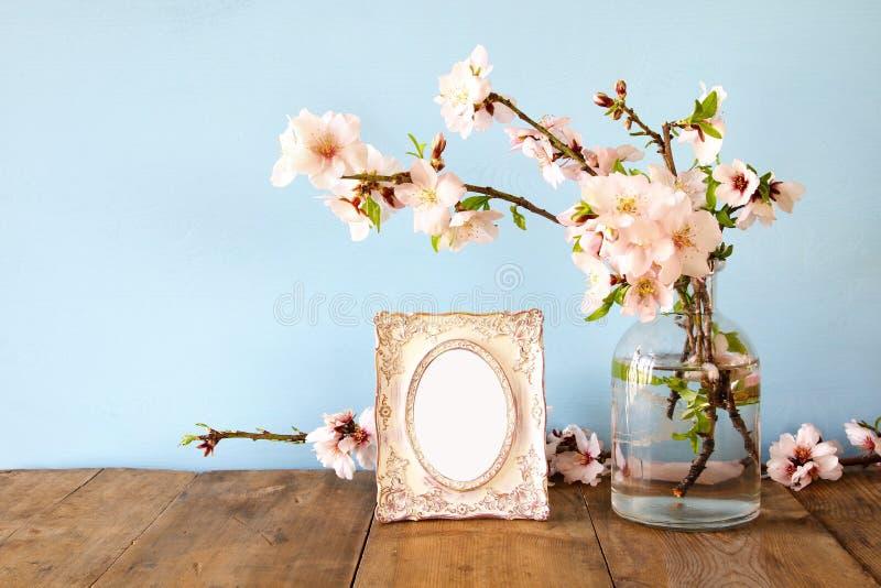 Quadro vazio da foto do vintage ao lado das flores da mola foto de stock