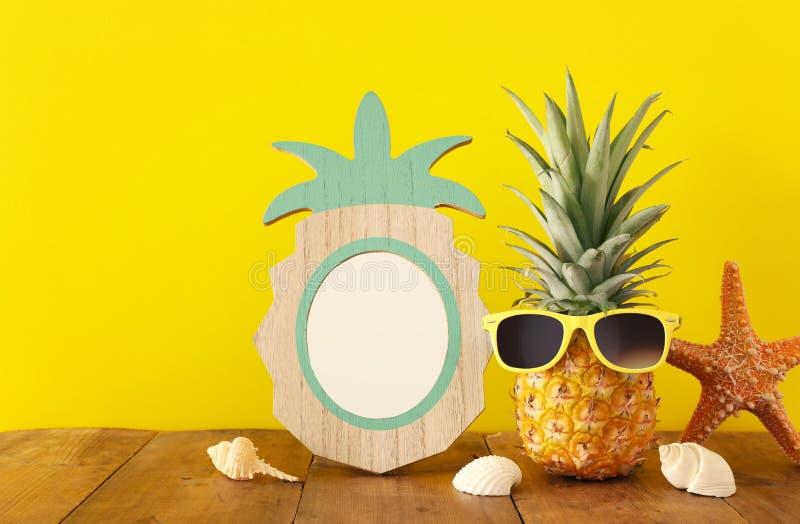 Quadro vazio da foto e abacaxi engraçado com óculos de sol Para a montagem da fotografia e do ?lbum de recortes imagens de stock royalty free