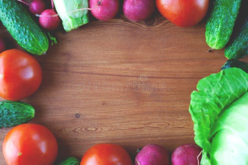 Quadro vegetal para a massa dos pepinos, rabanete, tomates, na opinião superior do fundo de madeira, estilo de vida fotografia de stock