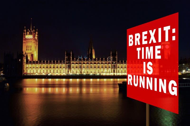Quadro vermelho com a frase & x27;Brexit: O tempo está em execução& x27; Brexit Concept com o parlamento em segundo plano à noite fotografia de stock