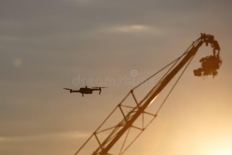 Quadrocopter-Brummen mit Fernbedienung gegen die Fernsehkamera, die am Kran hängt lizenzfreies stockfoto