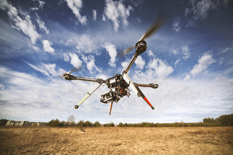 Quadrocopter drone flying in the sky stock photos
