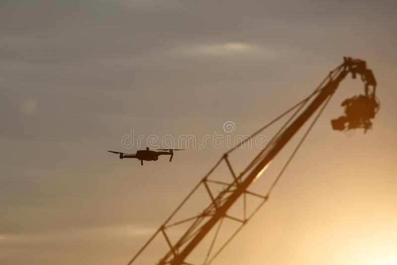 Quadrocopter drone with remote control vs Television Camera hanging on crane. Dark silhouette against colorfull sunset royalty free stock photo