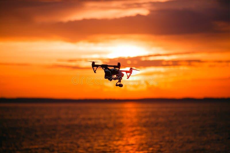 Quadrocopterhommel met afstandsbediening Donker silhouet tegen colorfullzonsondergang Zachte nadruk Gestemd beeld royalty-vrije stock afbeeldingen