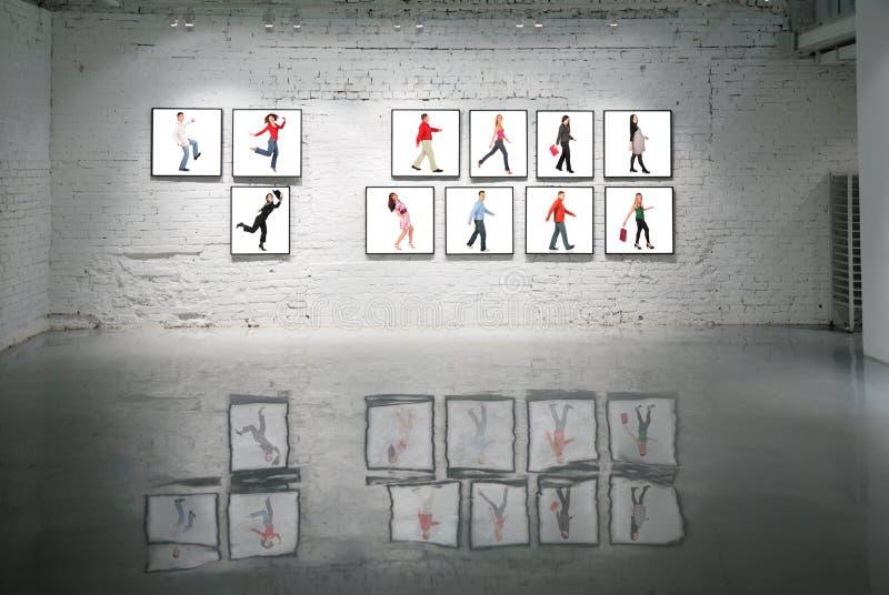 Quadros com os povos de passeio na parede de tijolo branca imagem de stock