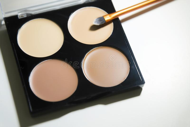 Quadruple skin tone eye concealer and contour palette with a beauty brush on a white background royalty free stock photos