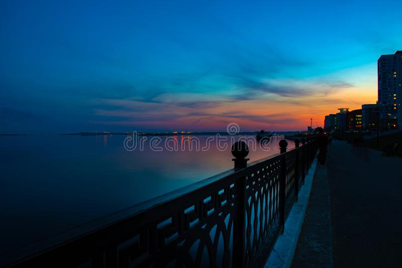 Quai de Saratov de ville de nuit de ressort sous le coucher du soleil Lumières décoratives de rue et beau ciel image stock