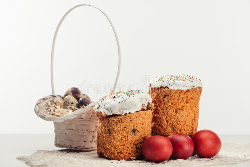 View of painted eggs in basket, willow twigs and delicious easter cakes. Quail eggs in basket, easter cakes and painted chicken eggs on grey stock photo