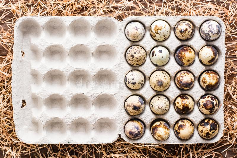 Quail eggs in a box and straw on a wooden table. Top view stock image