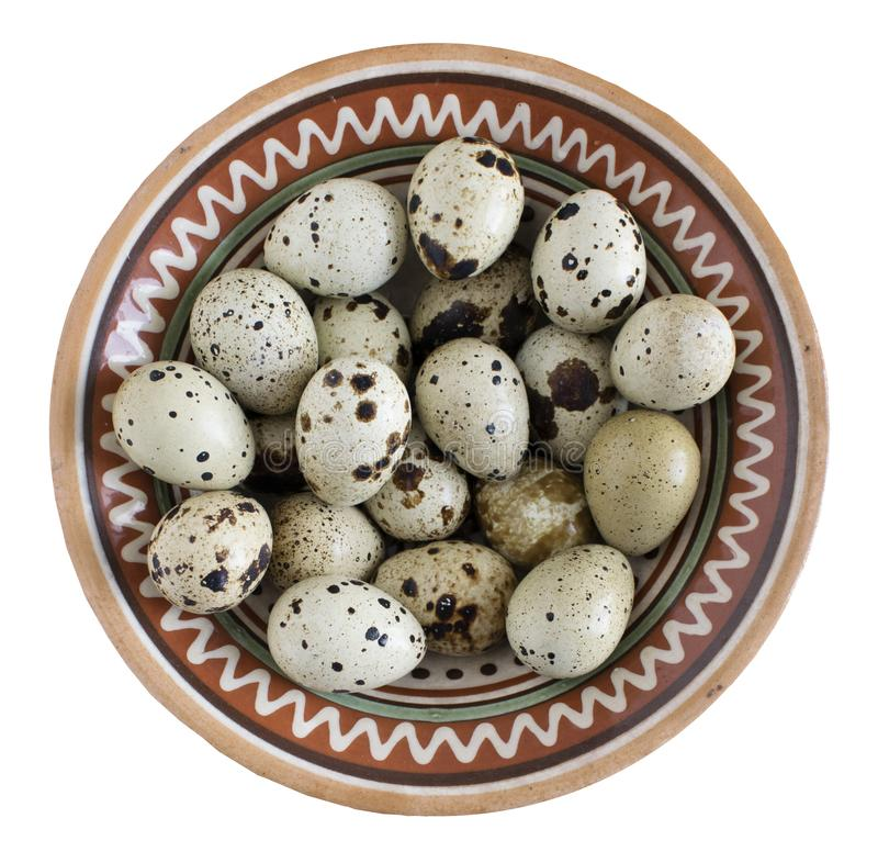 Quail eggs in a clay bowl with a pattern. Isolated on white royalty free stock photography