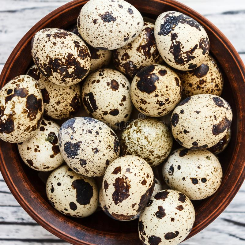 Quail eggs in a clay plate on a wooden background, a plate for storing quail eggs, a symbol of the Easter season. Healthy eating.  royalty free stock photography
