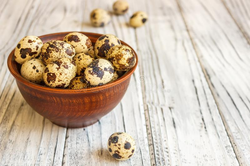 Quail eggs in a clay plate on a wooden background, a plate for storing quail eggs, a symbol of the Easter season. Healthy eating.  royalty free stock images