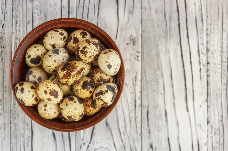 Quail eggs in a clay plate on a wooden background, a plate for storing quail eggs, a symbol of the Easter season. Healthy eating.  royalty free stock image