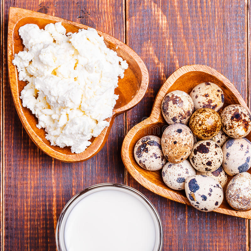 Quail eggs, cottage cheese, milk. On a wooden brown background royalty free stock images