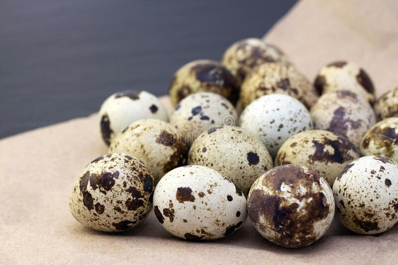 Quail eggs. On craft paper on a dark background royalty free stock photos