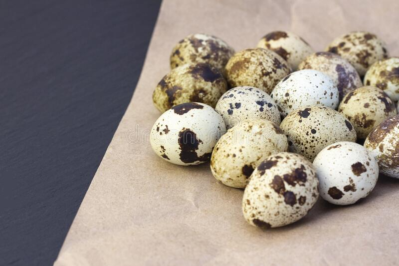 Quail eggs. On craft paper on a dark background stock photo