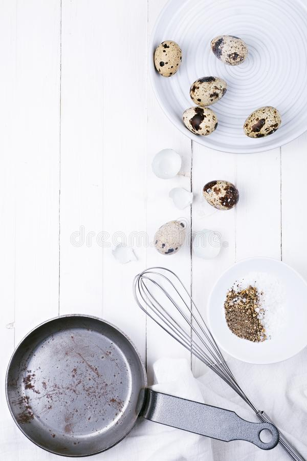 Quail eggs in a plate, a shell, a whisk for beating and a frying pan on a white wooden background. view from above royalty free stock images