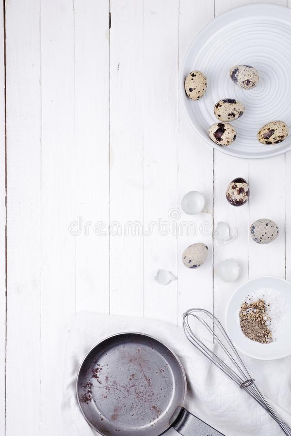 Quail eggs in a plate, a shell, a whisk for beating and a frying pan on a white wooden background. view from above stock photo