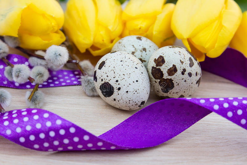 Quail eggs on the table with flowers and ribbon, tape royalty free stock photos
