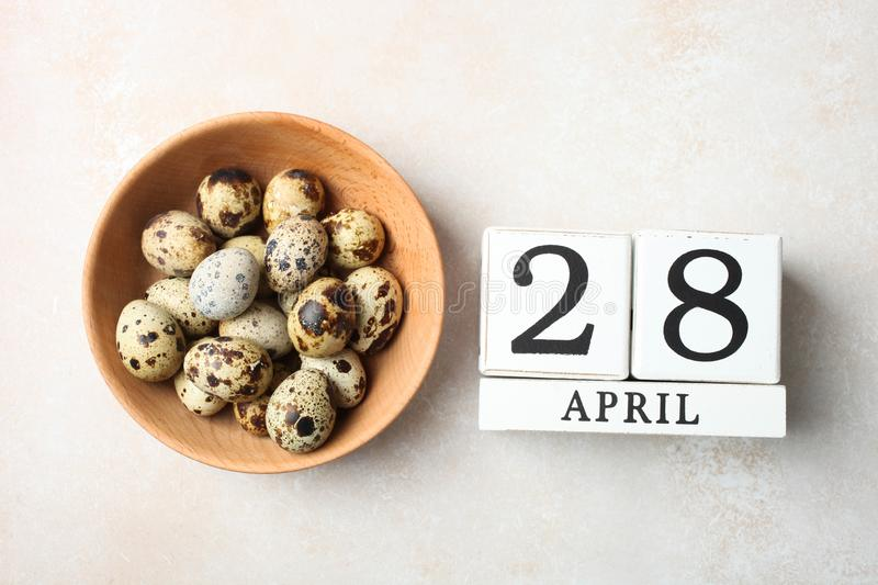 Quail eggs and wooden calendar. Concept holiday Easter. Bowl with quail eggs and wooden calendar with date of April 28 on neutral background. Concept holiday royalty free stock photo