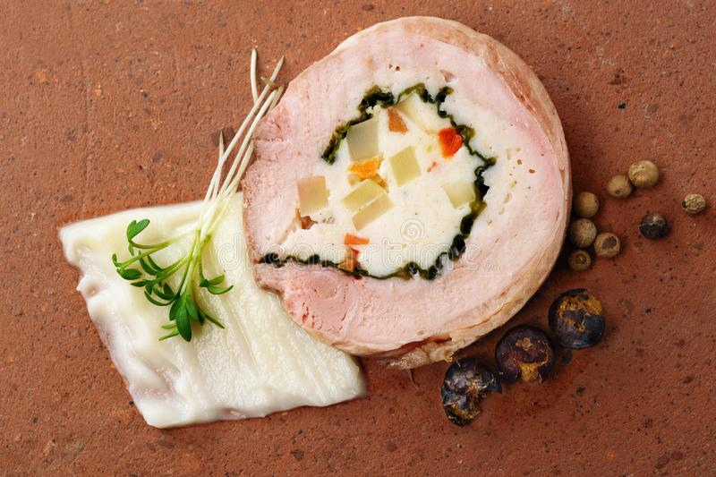 Quail galantine, de-boned stuffed meat for a festive dinner on a rustic brick plate, copy space, high angle view from above royalty free stock photography