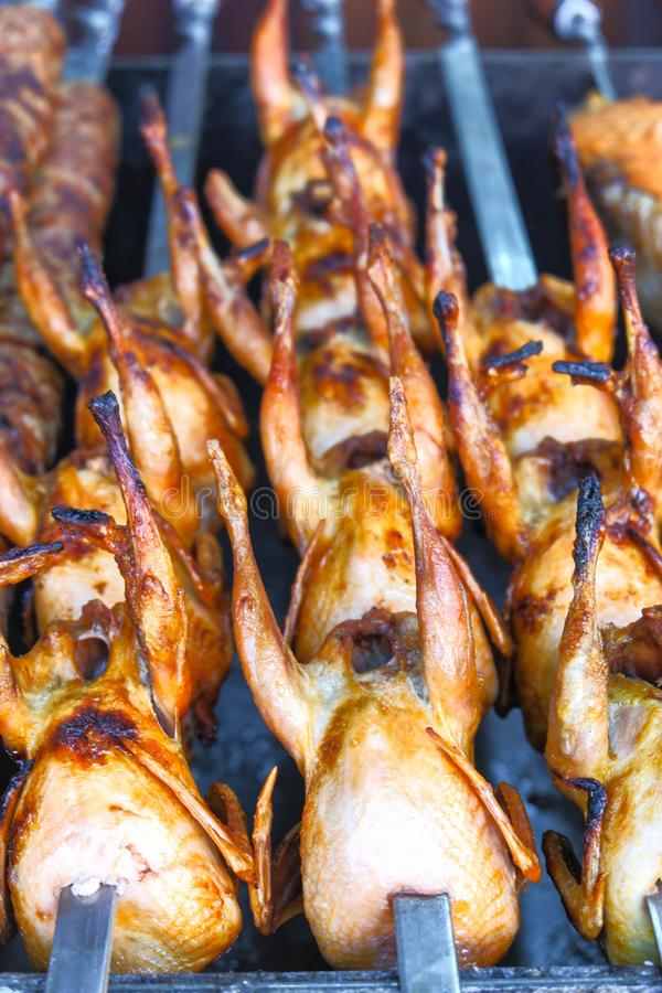 Quail kebab on skewers on the grill close-up stock images