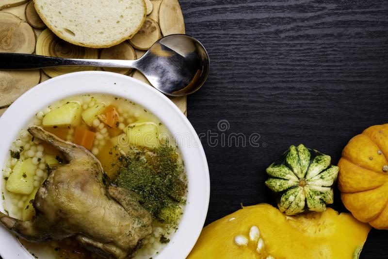 Quail pumpkin Soup, Broth with couscous and Vegetables Served with Bread on wooden table, small pumpkin copy space stock photo