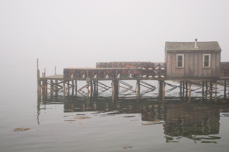 Quaint fishing wharf in fog. A view of a fishing wharf and shack on Bass Harbor in dense, coastal Maine fog stock image