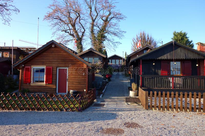 Swiss Village of Mini Summer Cottages. A quaint little neighborhood of wooden chalets for summer cabin retreat complete with walking path fenced yard and porches stock images