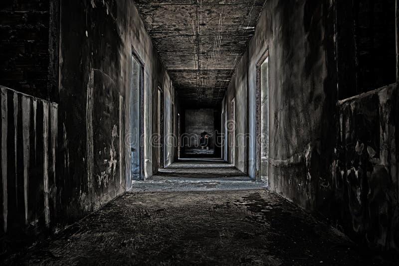qualche gente che si siede nella stanza alla conclusione del corridoio spaventoso fotografia stock libera da diritti