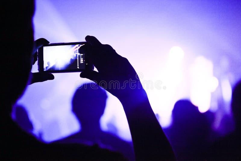 Qualcuno che parla un'immagine durante il concerto fotografia stock libera da diritti